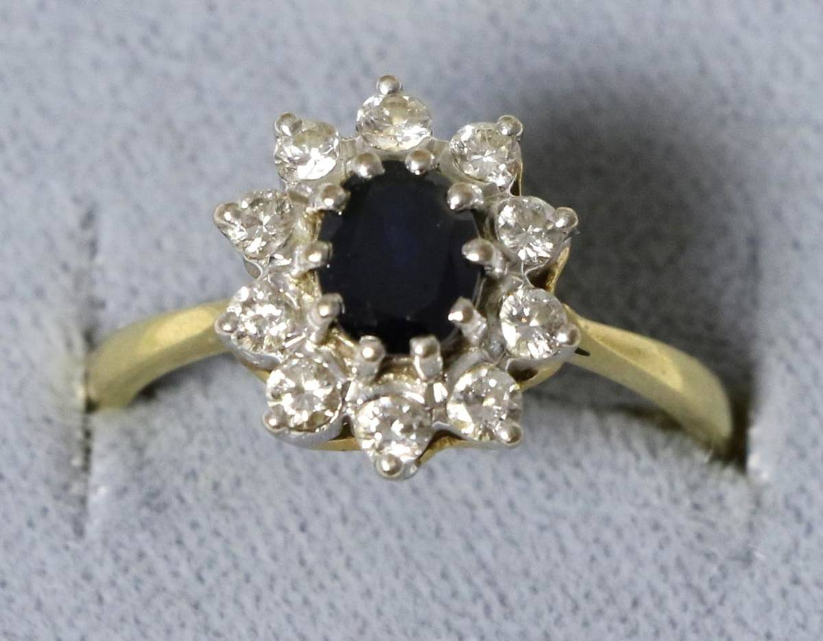 Lot 5 - An 18 carat gold sapphire and diamond cluster ring, an oval cut sapphire within a border of...