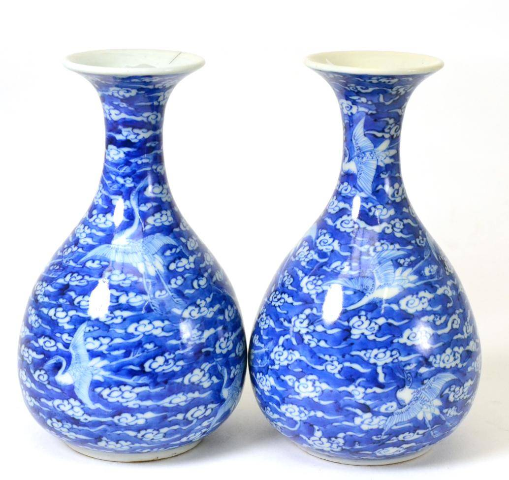 Lot 43 - A Pair of Chinese Porcelain Bottle Vases, 19th century, painted in underglaze blue with cranes...