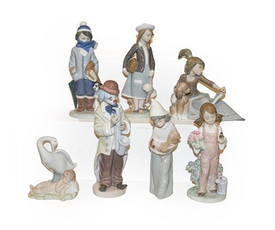Lot 20 - Eight Lladro figures including a clown playing...