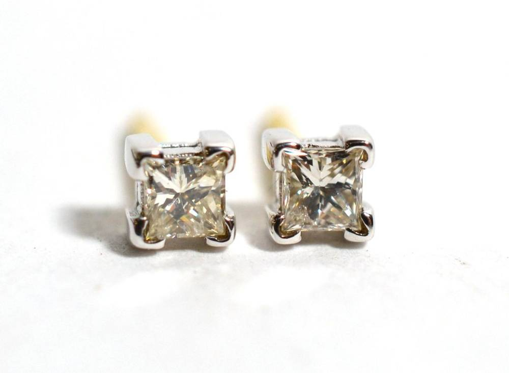 Lot 61 - A pair of 18 carat gold solitaire princess cut diamond earrings, in square claw settings, total...