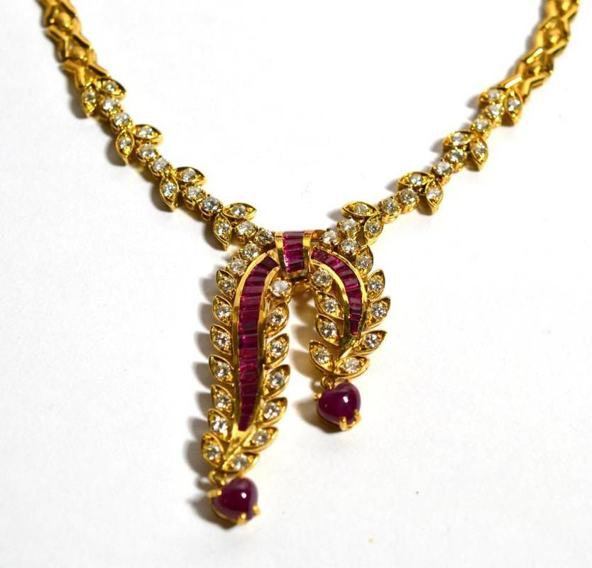 Lot 73 - A ruby and diamond necklace, a scroll front with channel set calibré cut ruby ribbons, with...