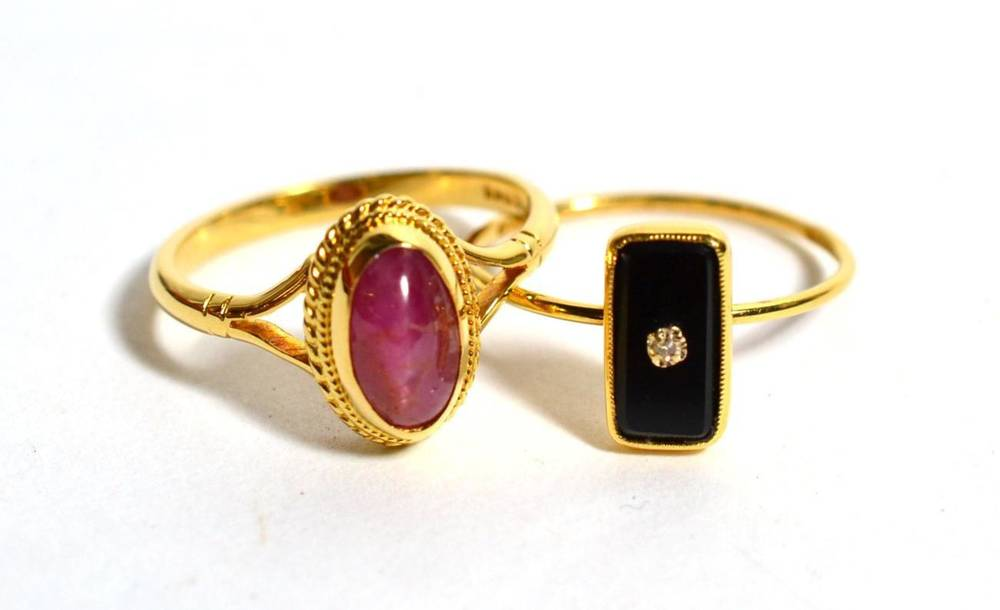 Lot 81 - An 18 carat gold onyx and diamond ring and an 18 carat gold cabochon ruby set ring, 5.3g gross (2)