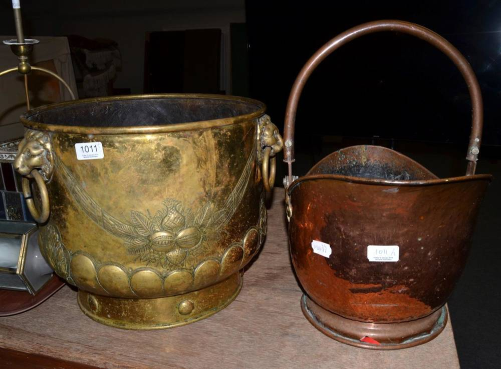 Lot 1011 - A Victorian brass log bin with three ring lion mask handles, together with a copper helmet form...