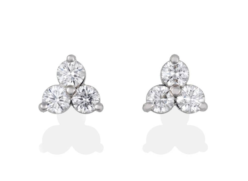 Lot 2032 - A Pair of 18 Carat White Gold Diamond Stud Earrings, trios of round brilliant cut diamonds in...