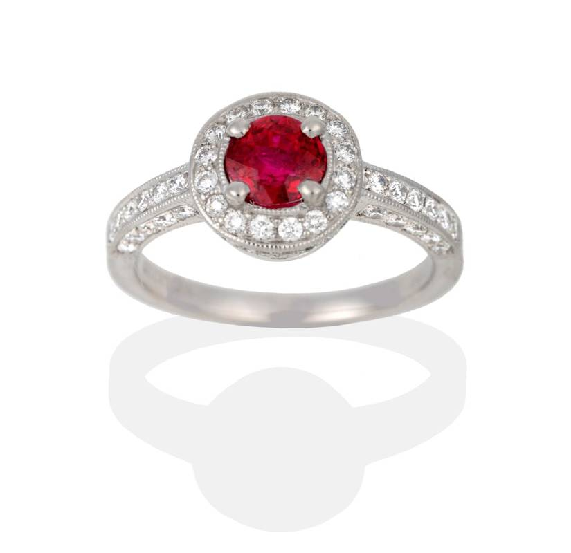 Lot 2040 - A Platinum Ruby and Diamond Cluster Ring, a round cut ruby in a claw setting, within a circular...