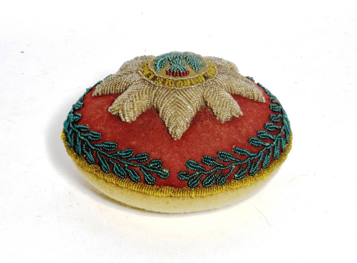 Lot 34 - An early 20th century beadwork pin cushion to the Scots Guards, of circular form, worked with...