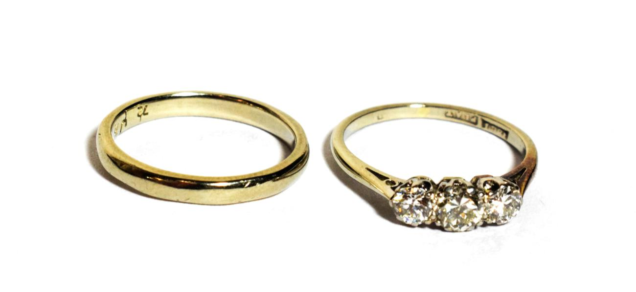 Lot 129 - An 18 carat white gold band ring, finger size J1/2; and a three stone diamond ring, stamped...