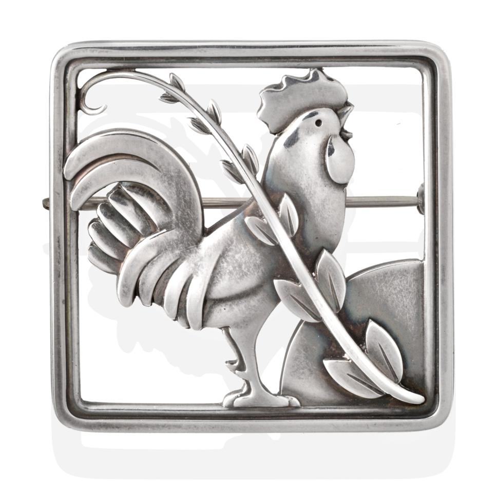 Lot 2020 - A Silver Brooch, by Georg Jensen, depicting a cockerel behind foliage within a square border,...