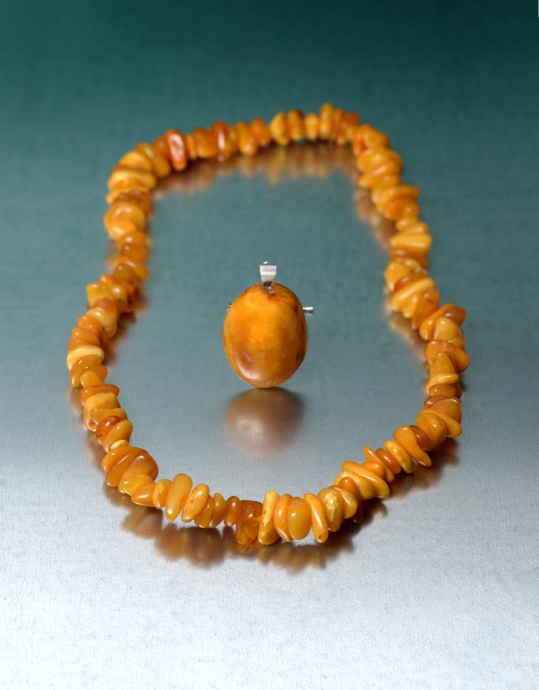 Lot 2025 - An Amber Necklace, comprising of one hundred and thirteen irregular shaped and sized orangey-yellow