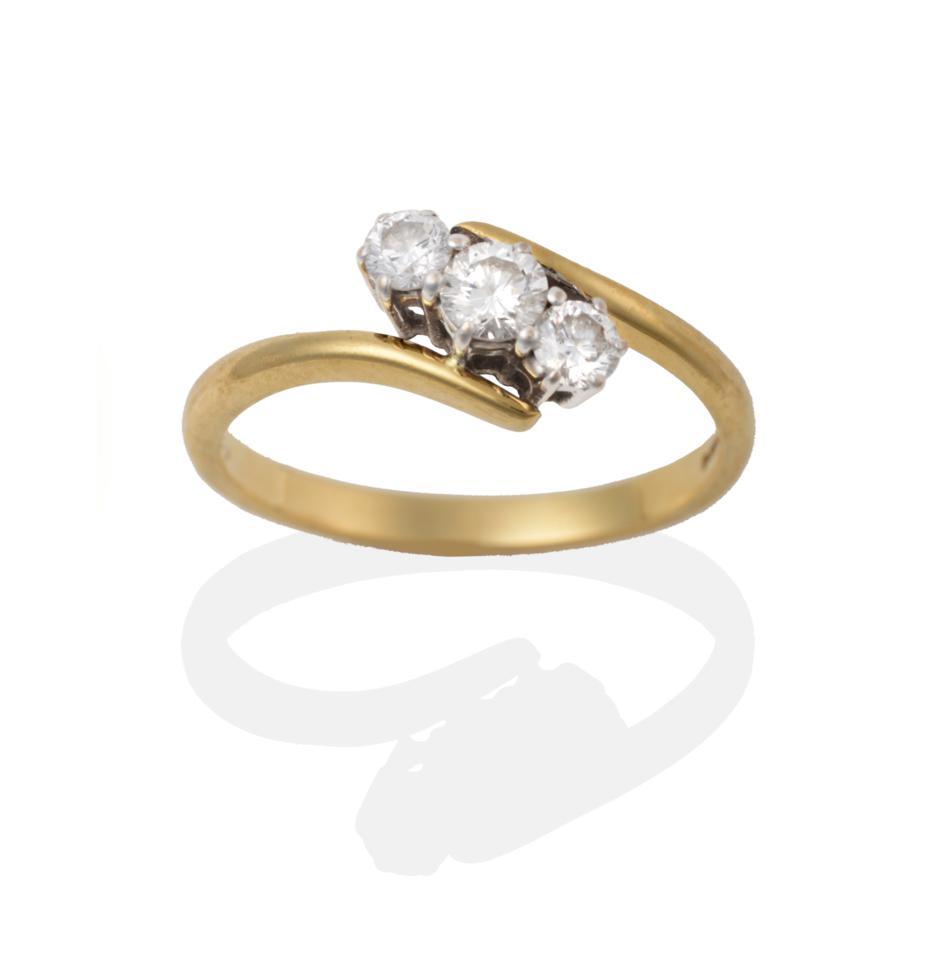 Lot 2026 - An 18 Carat Gold Diamond Three Stone Twist Ring, the round brilliant cut diamonds in white claw...