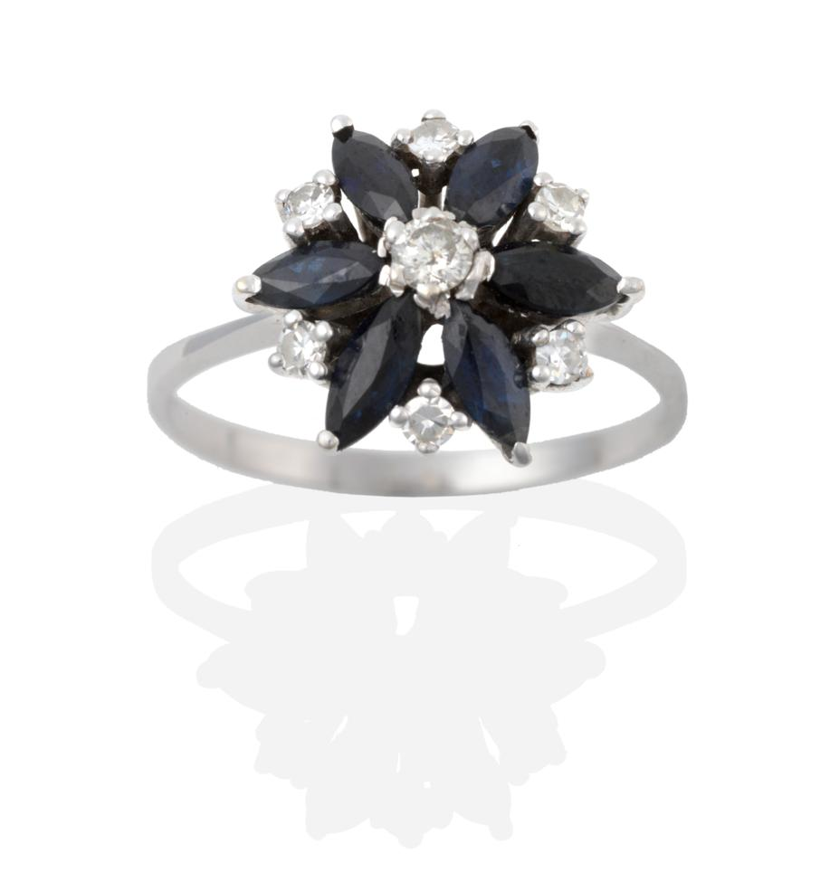 Lot 2039 - A Sapphire and Diamond Cluster Ring, a round brilliant cut diamond centres a cluster of six...