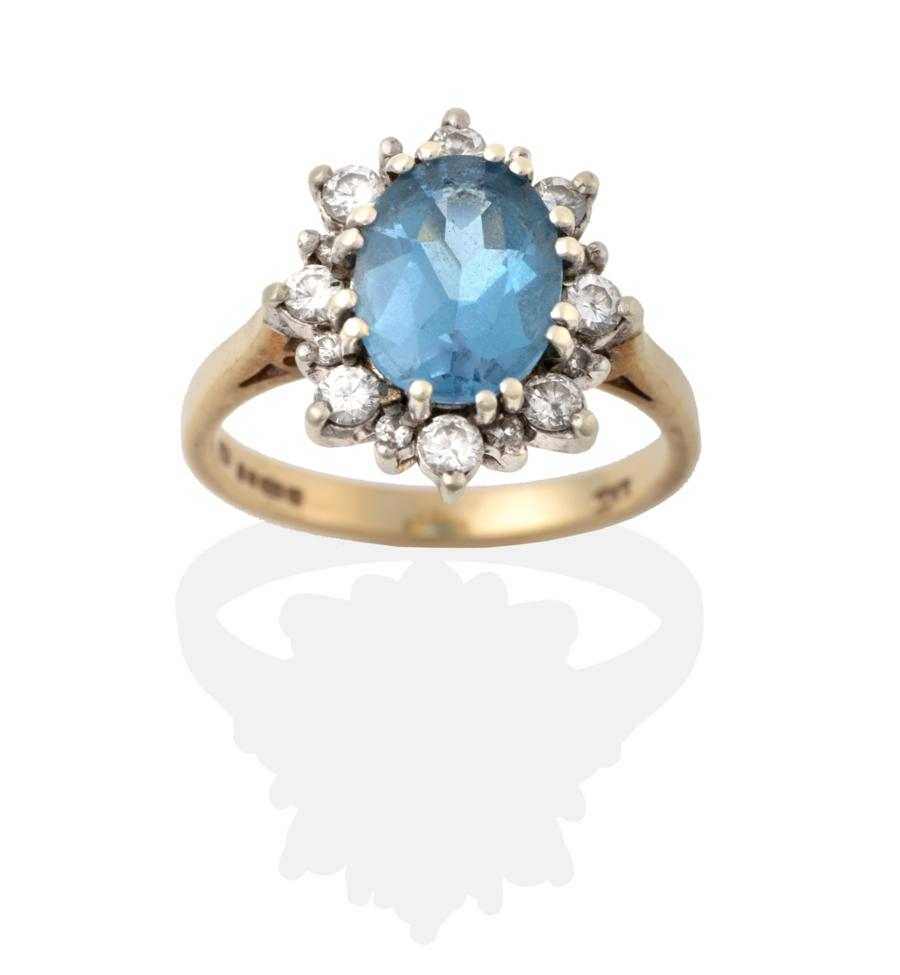 Lot 2042 - A 9 Carat Gold Blue Topaz and Diamond Cluster Ring, the oval cut blue topaz in a white double...