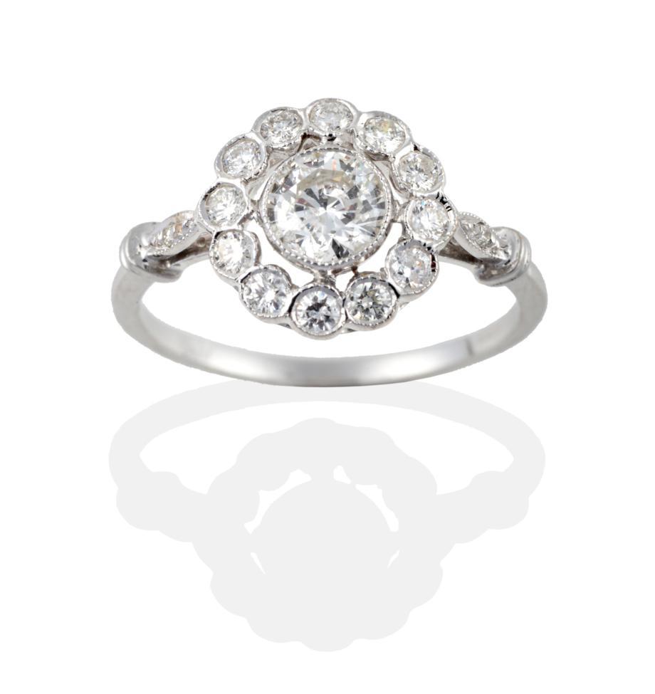 Lot 2045 - An 18 Carat White Gold Diamond Cluster Ring, the round brilliant cut diamonds in millegrain...