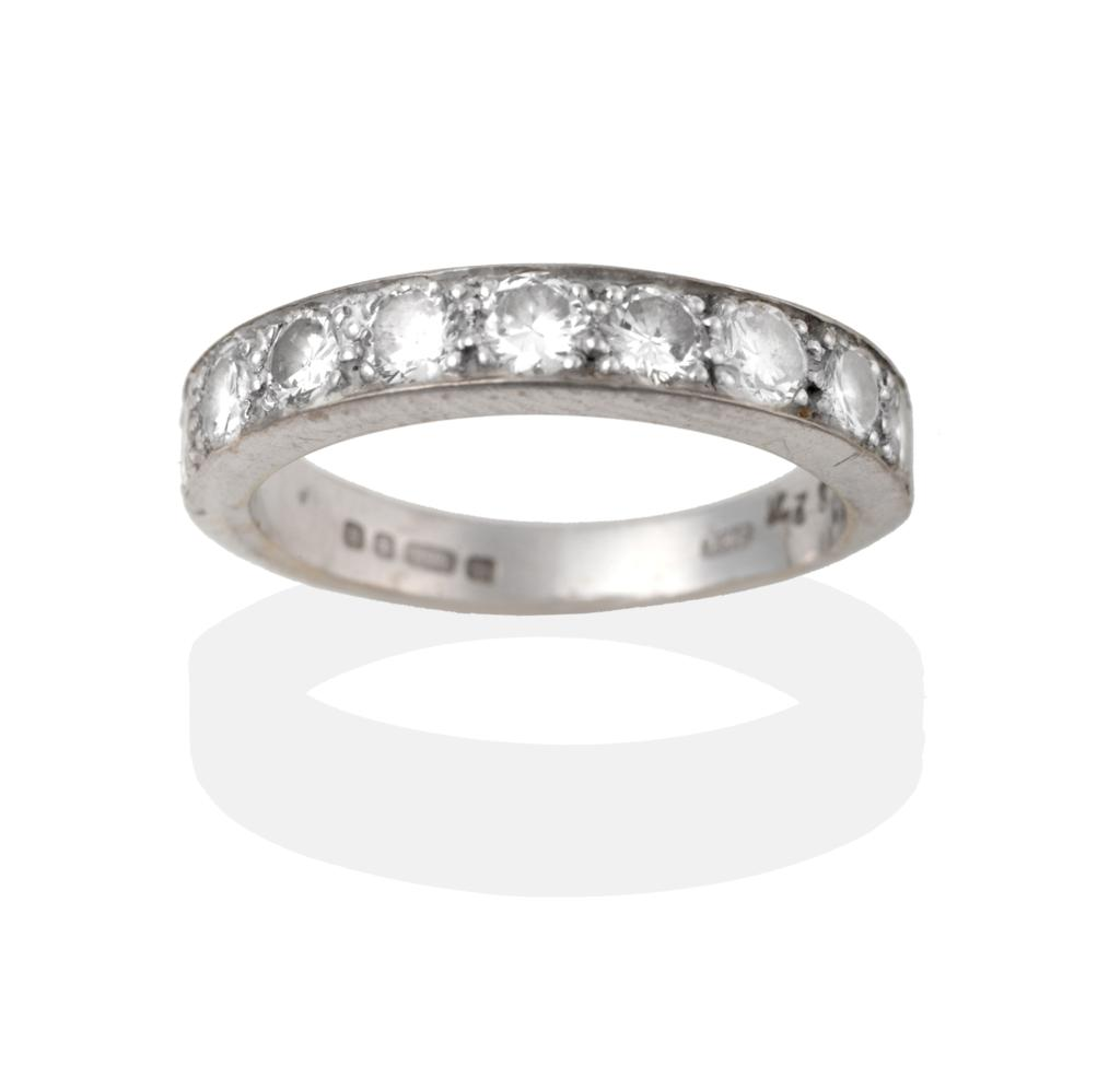 Lot 2048 - An 18 Carat White Gold Diamond Half Hoop Ring, nine round brilliant cut diamonds in white claw...
