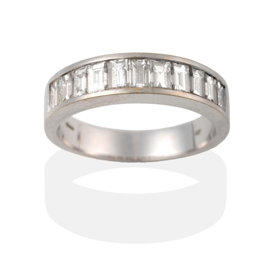 Lot 2050 - An 18 Carat White Gold Half Hoop Ring, eleven graduated baguette cut diamonds in a channel setting