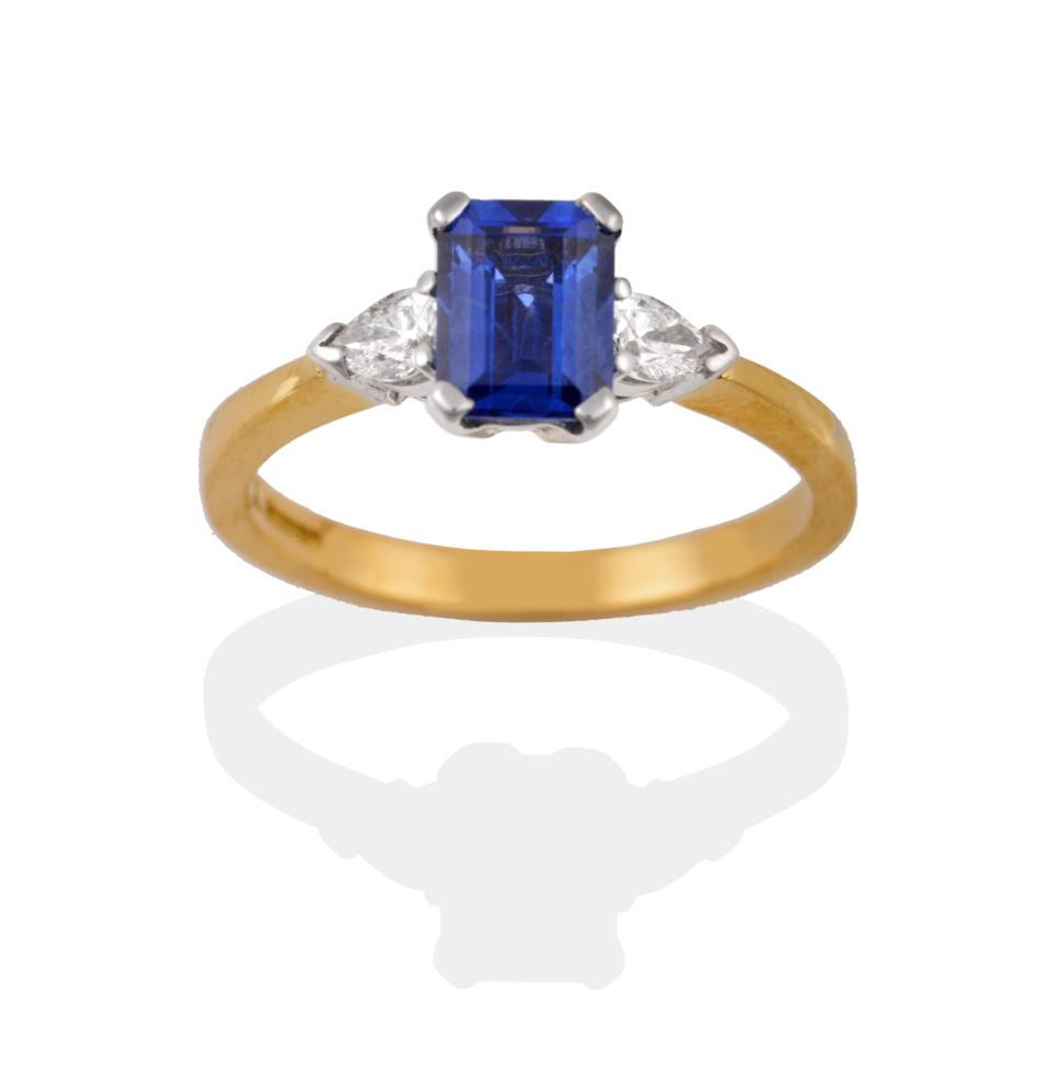 Lot 2058 - An 18 Carat Gold Sapphire and Diamond Three Stone Ring, the emerald-cut sapphire flanked by two...