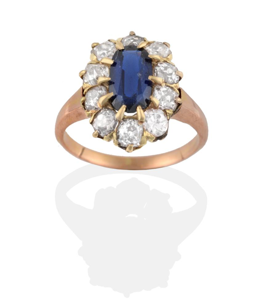 Lot 2090 - A Synthetic Sapphire and Diamond Cluster Ring, the oval cut synthetic sapphire within a border...