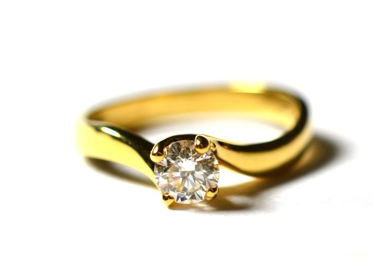 Lot 224 - An 18 carat gold solitaire diamond ring, a round brilliant cut diamond in a yellow claw setting, to