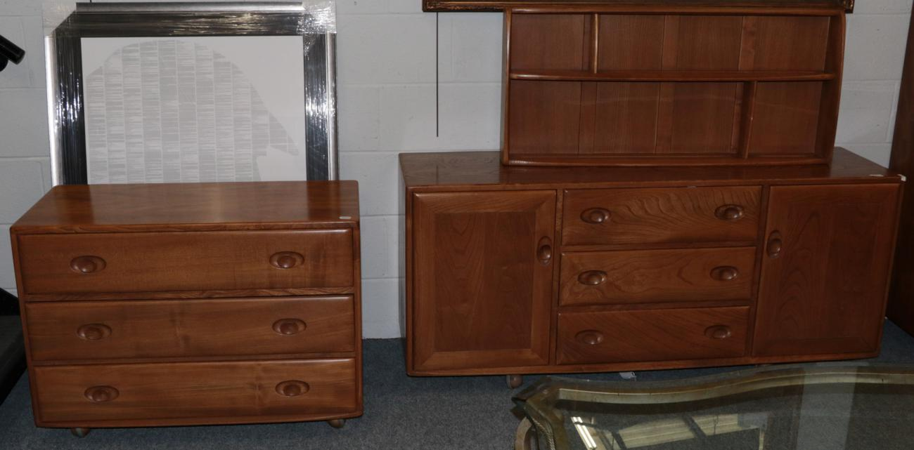 Lot 1001 - A 1960/70 Ercol Elm Windsor Sideboard, with three central drawers flanked by cupboard doors, on...