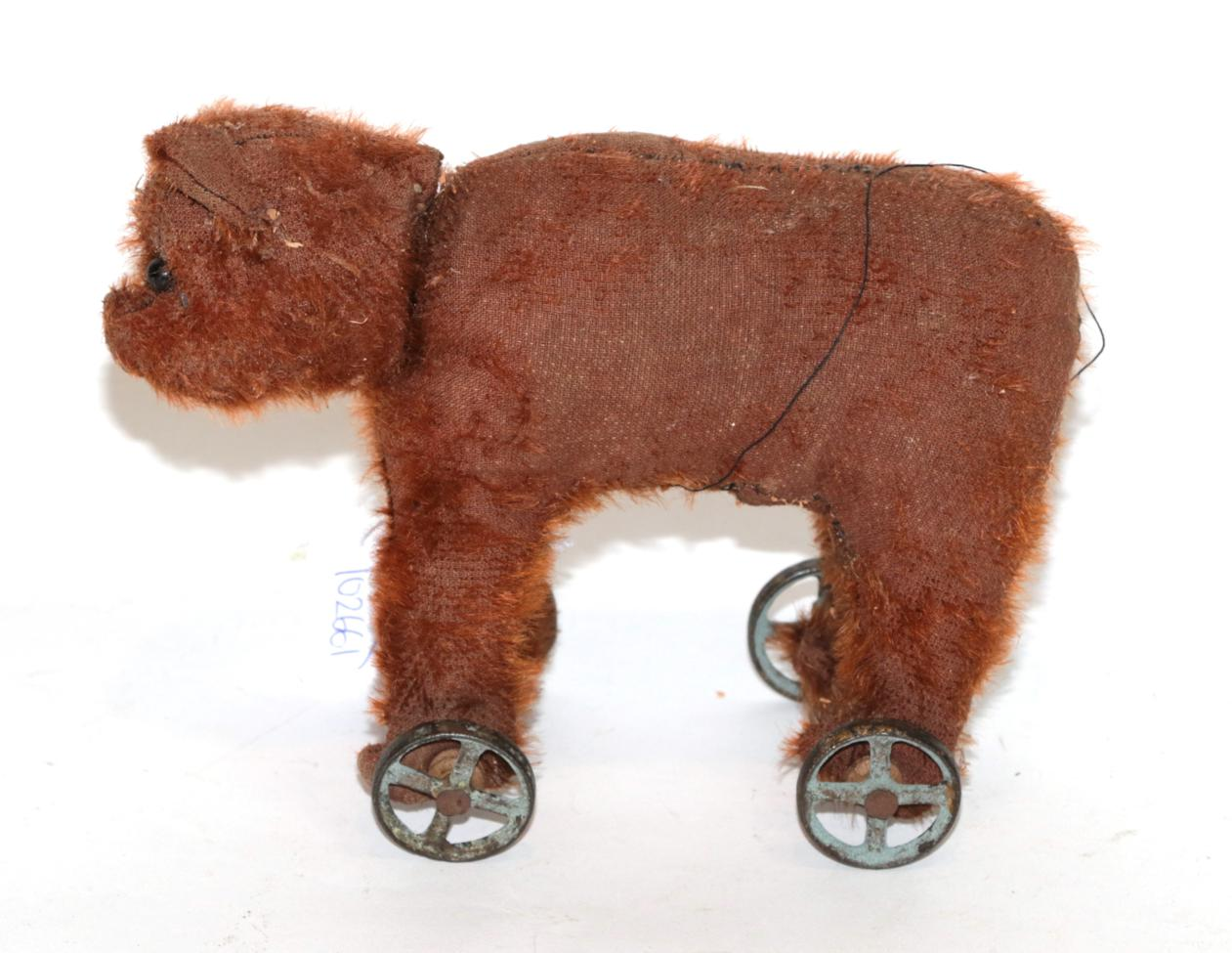 Lot 1022 - An early 20th century Steiff bear on wheels in red/brown mohair, boot button eyes, on four...