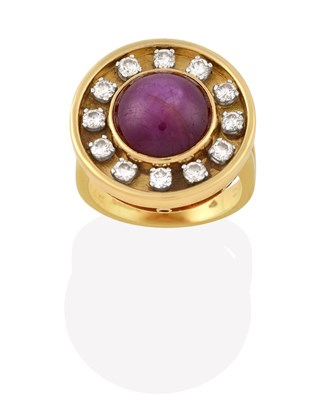 Lot 2019 - An 18 Carat Gold Ruby and Diamond Cluster Ring, the round cabochon ruby in a yellow rubbed over...