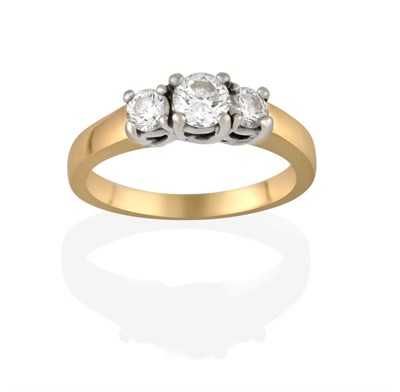 Lot 2027 - A Diamond Three Stone Ring, the graduated round brilliant cut diamonds in white claw settings, to a
