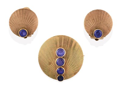Lot 2032 - A Sapphire Brooch, of yellow textured circular form with four graduated round cut sapphires in...