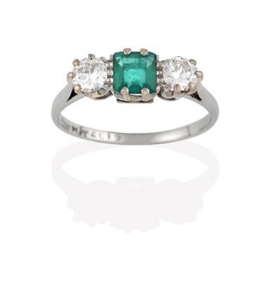 Lot 2043 - An Emerald and Diamond Three Stone Ring, the central step cut emerald flanked by round...