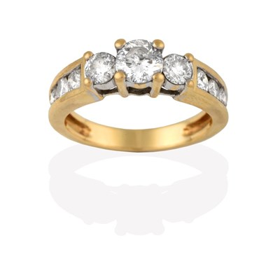 Lot 2073 - A Diamond Three Stone Ring, the graduated round brilliant cut diamonds in yellow claw settings,...