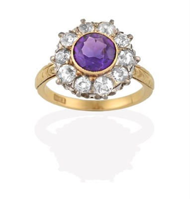 Lot 2076 - An Amethyst and Diamond Cluster Ring, the round cut amethyst in a yellow rubbed over setting,...
