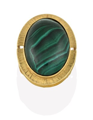 Lot 2084 - A Malachite Ring, the oval cabochon malachite in a yellow rubbed over setting to a further textured