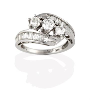 Lot 2089 - A Diamond Three Stone Twist Ring, the graduated round brilliant cut diamonds in white claw...