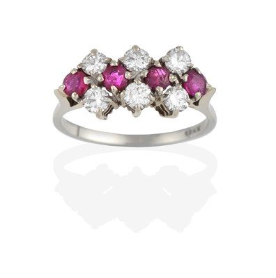 Lot 2093 - A Ruby and Diamond Cluster Ring, four round cut rubies spaced by three pairs of round brilliant cut