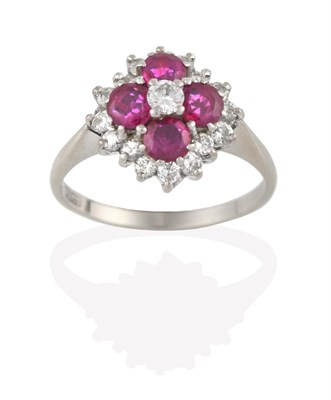 Lot 2094 - A Ruby and Diamond Cluster Ring, the central round brilliant cut diamond within a border of...