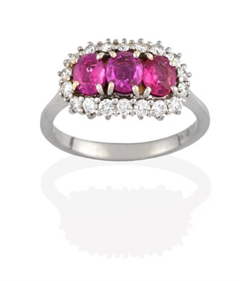 Lot 2095 - A Ruby and Diamond Cluster Ring, three oval cut rubies within a border of round brilliant cut...