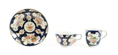Lot 55 - A Worcester Porcelain Trio, circa 1770, painted with the Queen's Japan pattern on a blue scale...