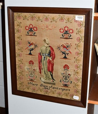 Lot 1022 - A needlework sampler, the central robed figure flanked by planters of flowers and birds, Mary...