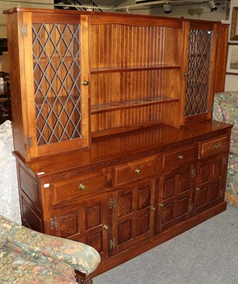 Lot 1068 - A modern oak dresser, the upper section with shelves and lead glazed doors, the lower section...