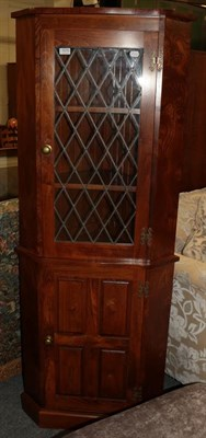 Lot 1070 - A modern oak standing corner cupboard with lead glazed upper section and panelled lower...