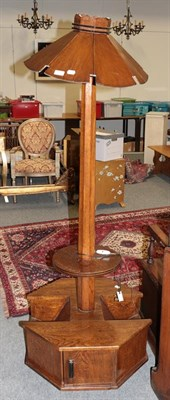 Lot 1074 - An Art Deco oak standard lamp with slatted shade on magazine rack and cupboard base, 177cm high