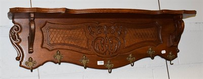 Lot 1089 - A carved oak hall rack with mask and scroll hooks, 110cm by 32cm by 25cm