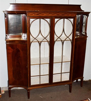 Lot 1090 - An Edwardian inlaid mahogany display cabinet, the two glazed doors flanked by mirrored recesses...