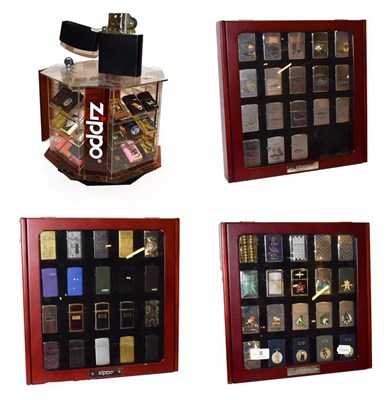 Lot 8 - ~ Three collectors display cases containing a total of fifty-seven Zippo lighters, a rotating...