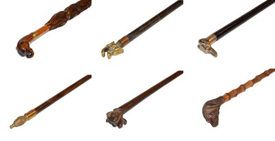 Lot 26 - ~ Four novelty walking canes, one carved in the form of an umbrella and each with a topper in...
