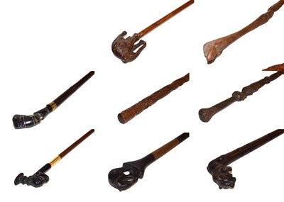 Lot 27 - ~ A collection of carved walking sticks including African hardwood examples with figural and...