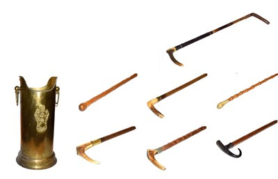 Lot 39 - ~ A brass stick stand with loop handles containing six walking sticks and a riding crop,...