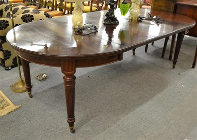 Lot 1099 - A mahogany wind out dining table raised on tapering reeded legs with three additional leaves, 240cm