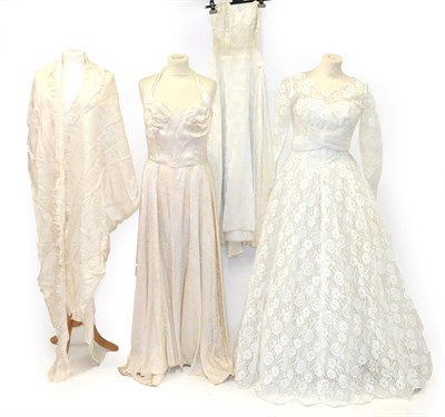 Lot 2072 - Three Early 20th Century Wedding Dresses, comprising a cream silk halter neck dress, woven with...
