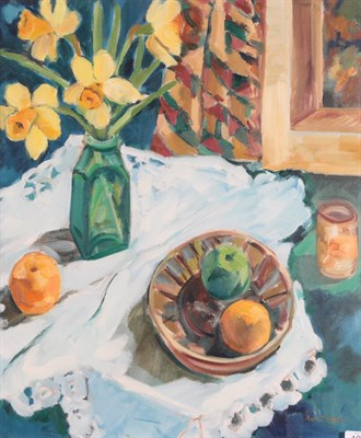 Lot 1055 - Anne Mendelow (b.1945) Still life of daffodils in a green vase and fruit on a white tablecloth...