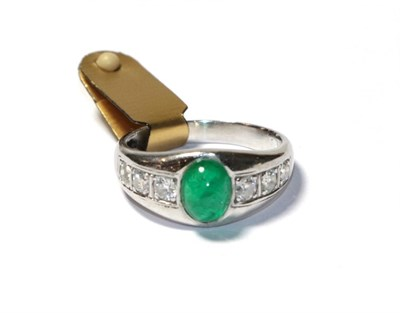 Lot 52 - An emerald and diamond ring, the cabochon emerald in a white collet setting, to shoulders inset...
